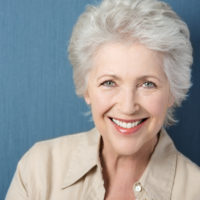 Beautiful elegant elderly lady with a lively smile looking directly at the camera while posing against a green background with copyspace