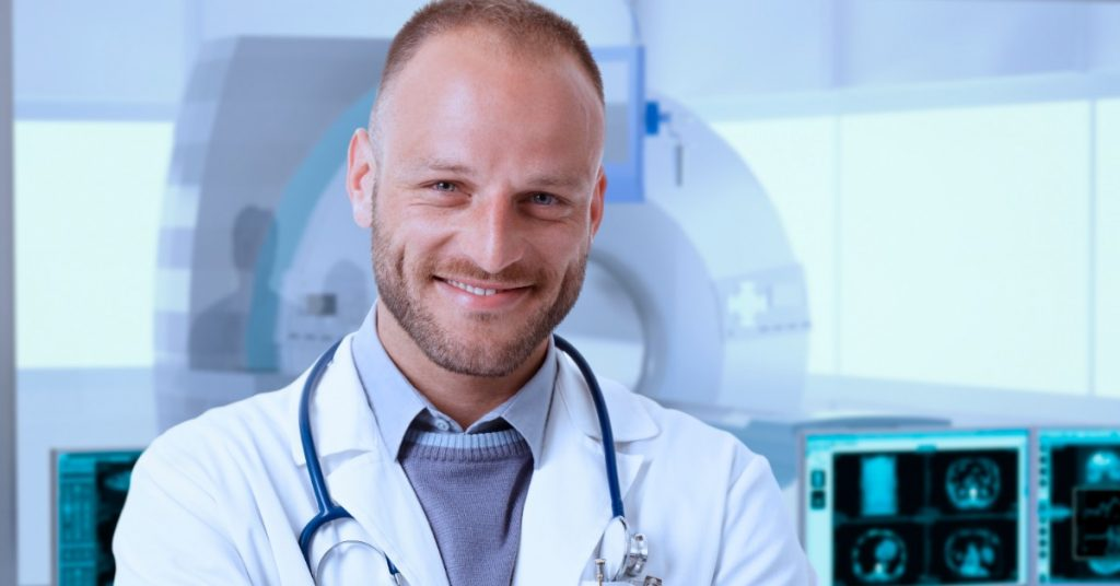 image of a white man in a lab coat and a stethoscope around his neck with arms crossed standing in front of MRI machine smiling at the camera