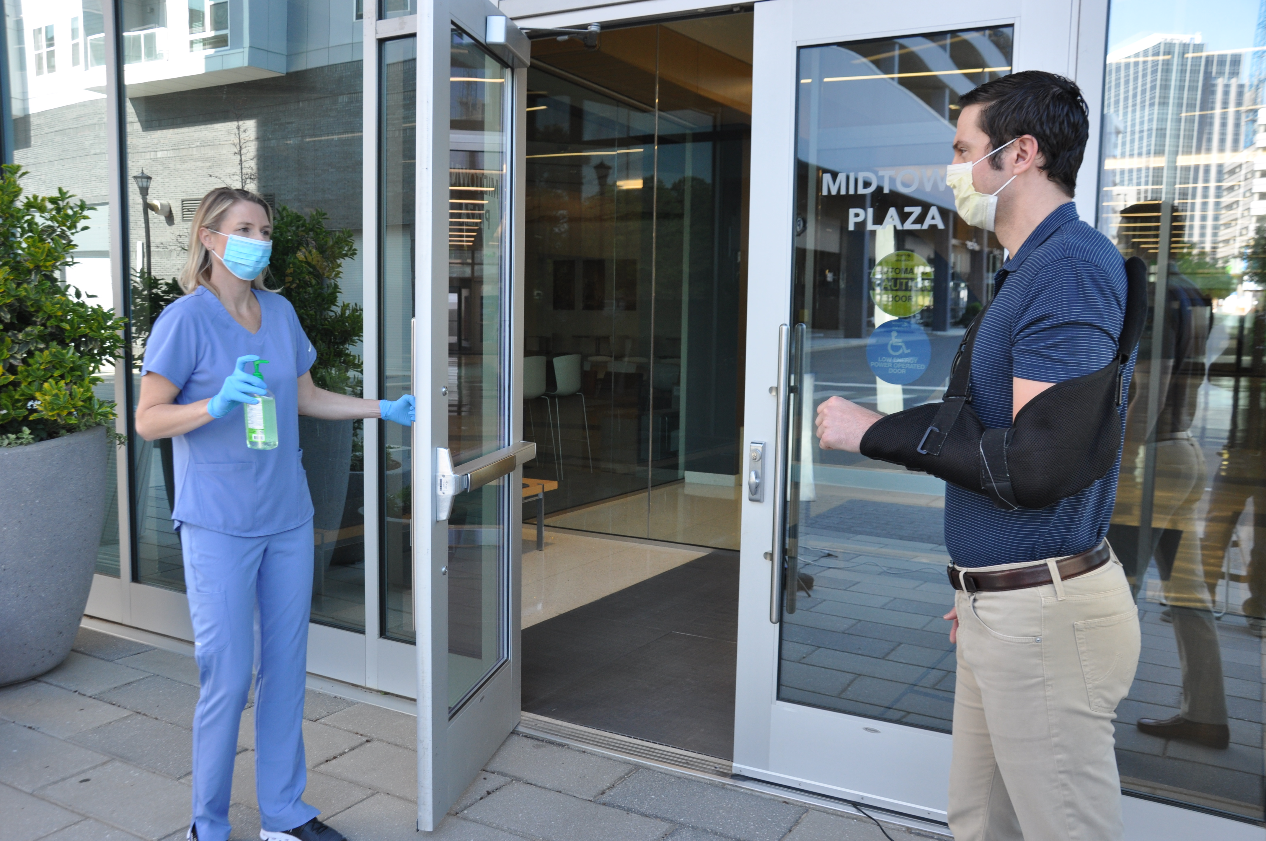 image of staff member in mask and gloves holding the door open for a patient with arm in sling