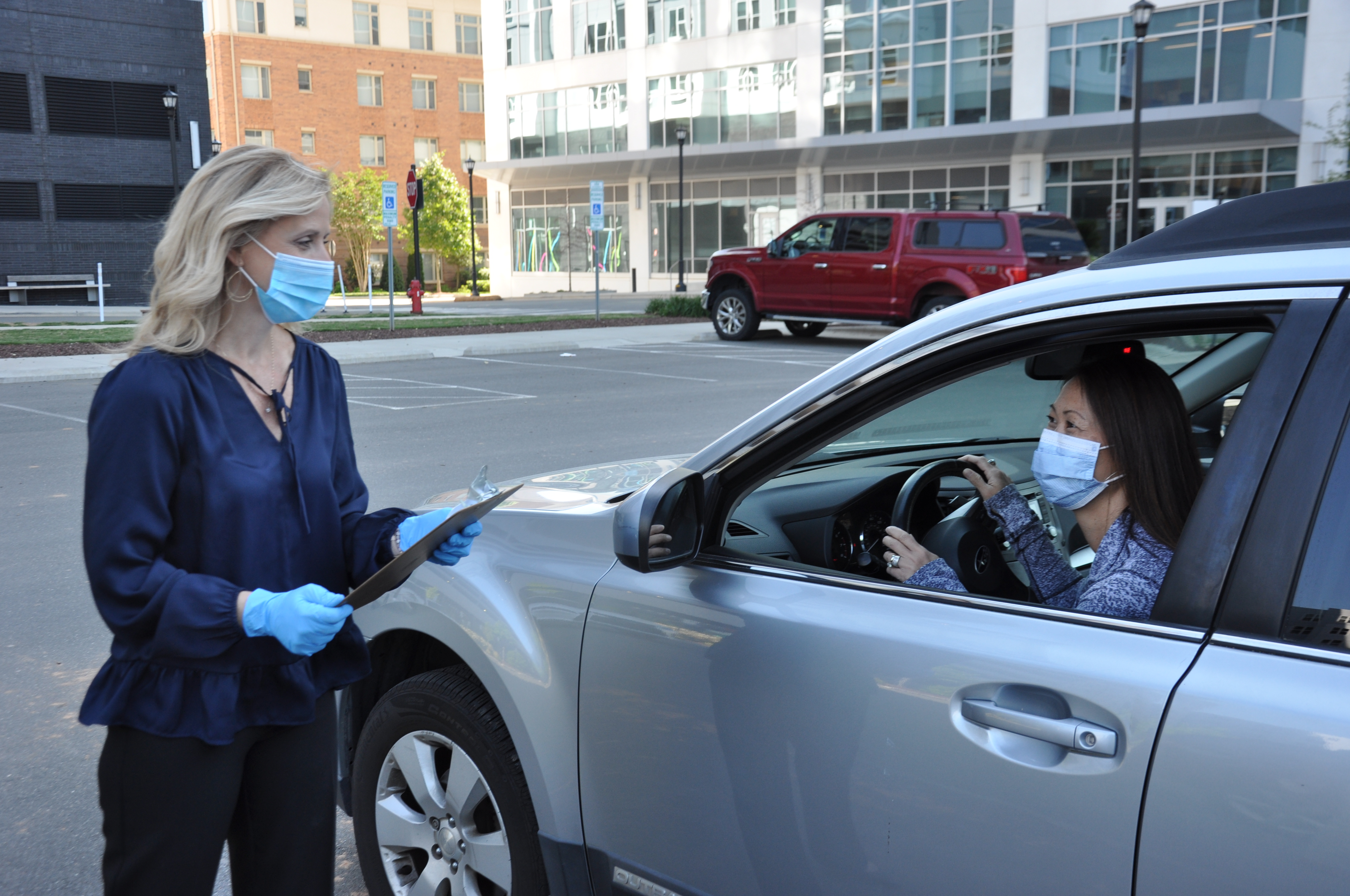 image of staff member in gloves and mask approaching patient wearing a mask in car